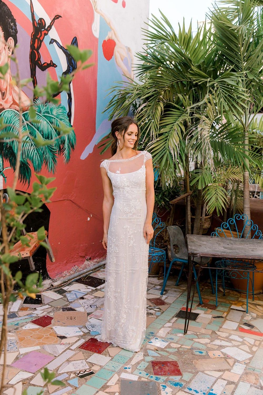 Model wearing Vinka Design Lola Wedding Dress, a Boat-Neck Lace Wedding Gown in the colourful street art streets of Havana