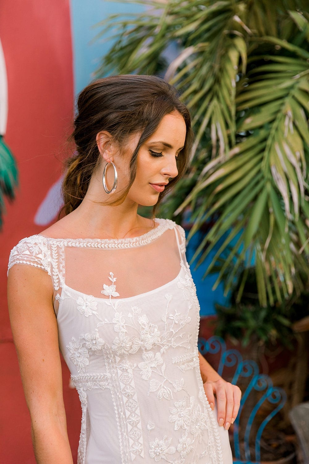 Model wearing Vinka Design Lola Wedding Dress, a Boat-Neck Lace Wedding Gown close up in the colourful streets of Havana