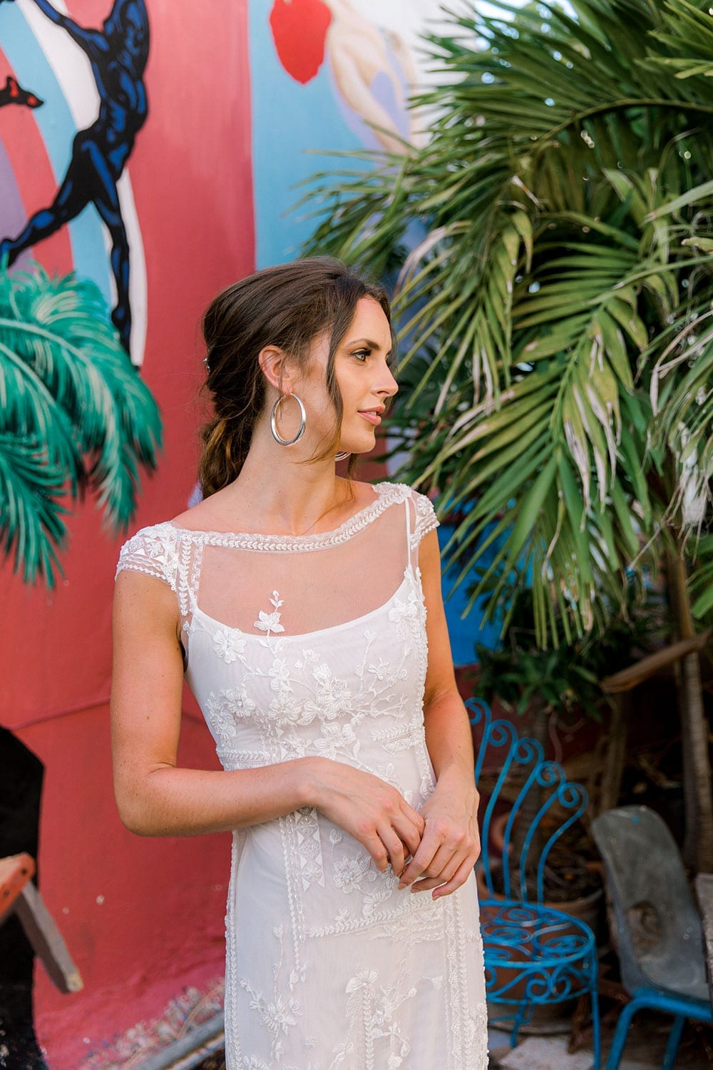 Model wearing Vinka Design Lola Wedding Dress, a Boat-Neck Lace Wedding Gown close up in the colourful and green streets of Havana