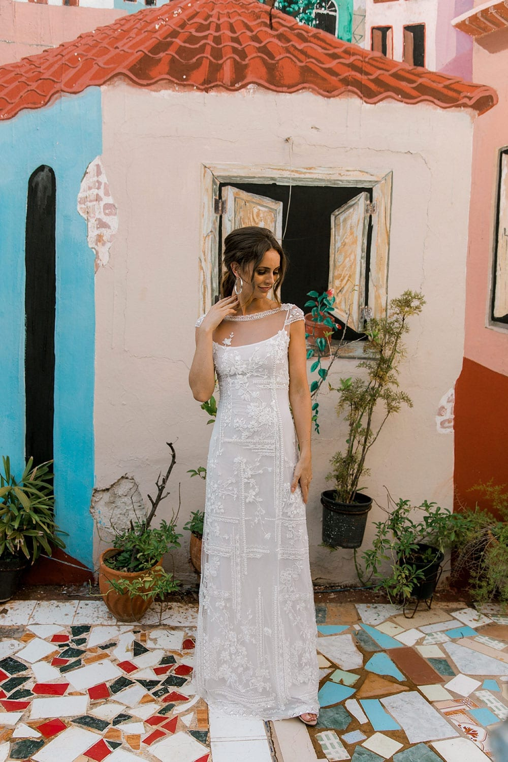 Model wearing Vinka Design Lola Wedding Dress, a Boat-Neck Lace Wedding Gown close up in the colourful back streets of Havana