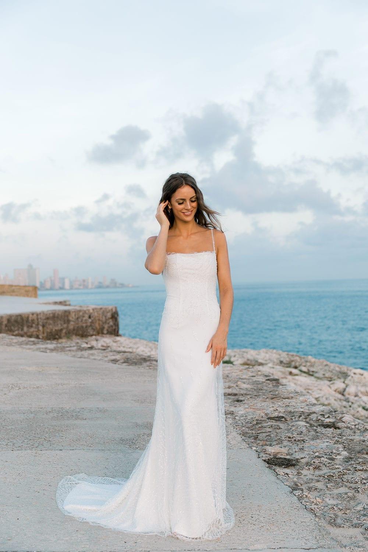 Model wearing Vinka Design Lolita Wedding Dress, a Fitted Beaded Wedding Gown on the sea wall of Havana