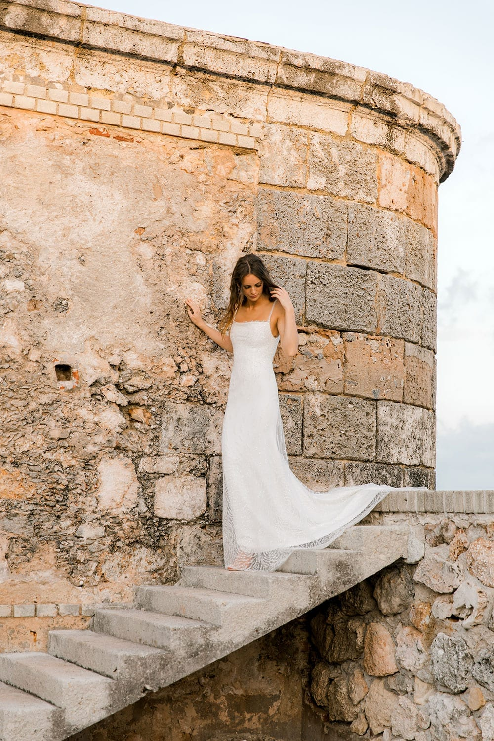 Model wearing Vinka Design Lolita Wedding Dress, a Fitted Beaded Wedding Gown next to the sea wall and ruins of Havana