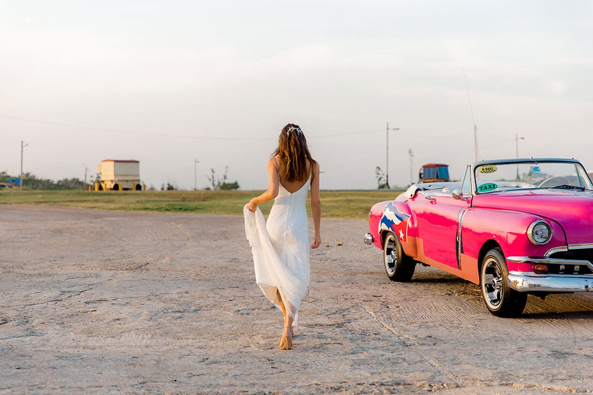 Model wearing Vinka Design Lolita Wedding Dress, a Fitted Beaded Wedding Gown walking in Havana with a classic car in the background