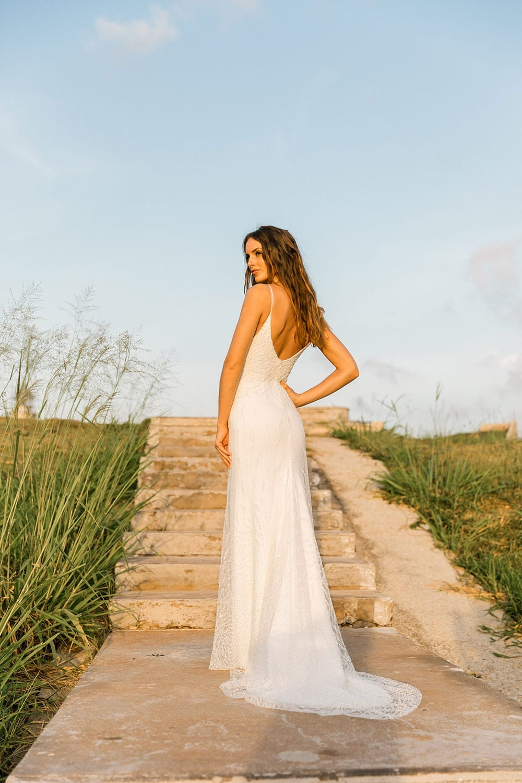 Model wearing Vinka Design Lolita Wedding Dress, a Fitted Beaded Wedding Gown on a path in Havana