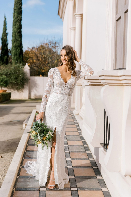 Model wearing Vinka Design Nadene Wedding Dress, a Long Sleeve Lace Wedding Gown outside grand old building and garden