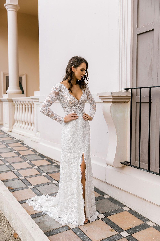 Model wearing Vinka Design Nadene Wedding Dress, a Long Sleeve Lace Wedding Gown outside grand old building tiled pathway