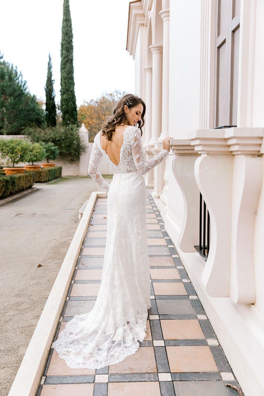 Model wearing Vinka Design Nadene Wedding Dress, a Long Sleeve Lace Wedding Gown outside grand old building tiled pathway walking away