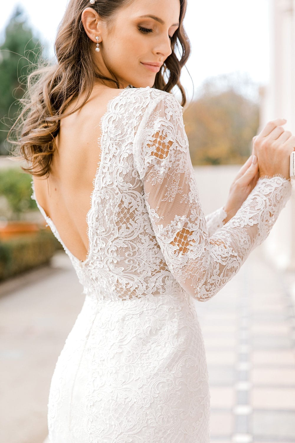 Model wearing Vinka Design Nadene Wedding Dress, a Long Sleeve Lace Wedding Gown outside old building with beautiful garden close up facing away
