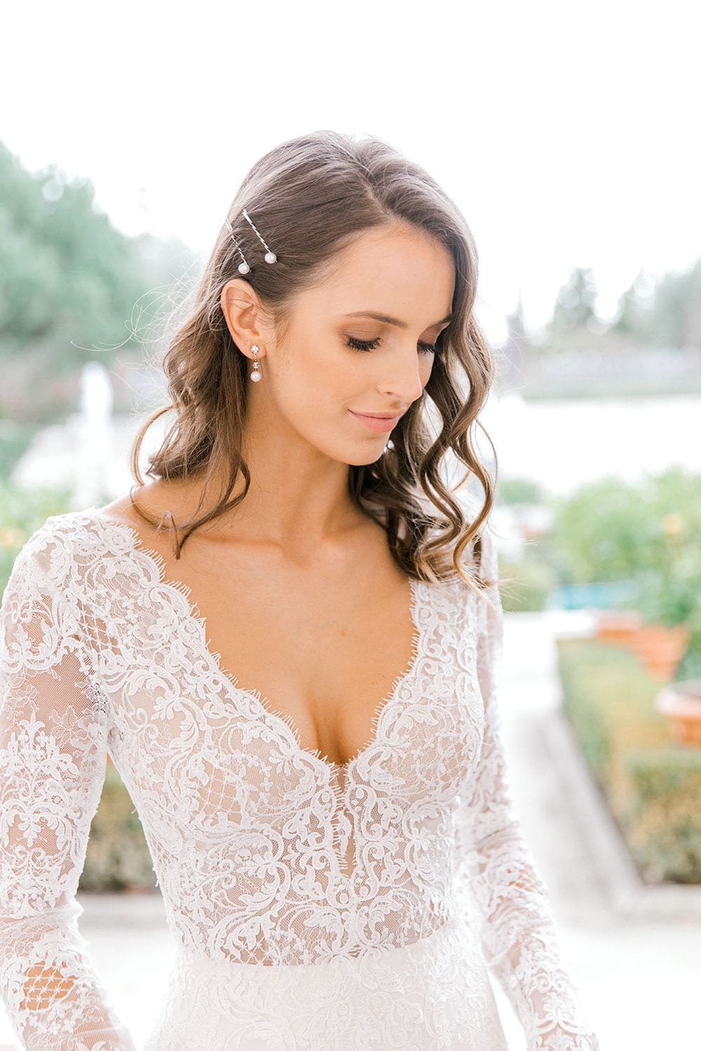 Model wearing Vinka Design Nadene Wedding Dress, a Long Sleeve Lace Wedding Gown outside old building with beautiful garden close up