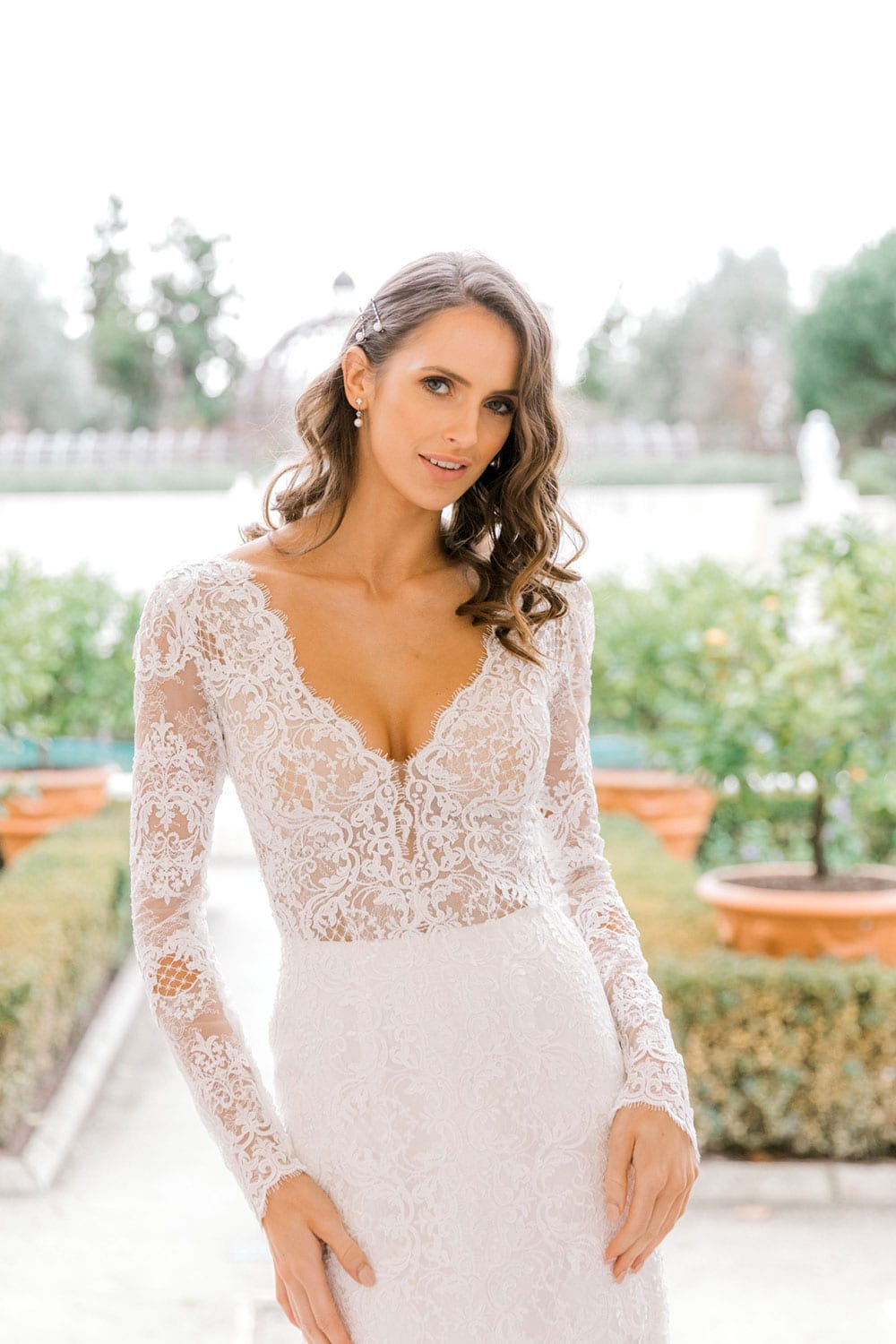 Model wearing Vinka Design Nadene Wedding Dress, a Long Sleeve Lace Wedding Gown outside old building with beautiful garden in background