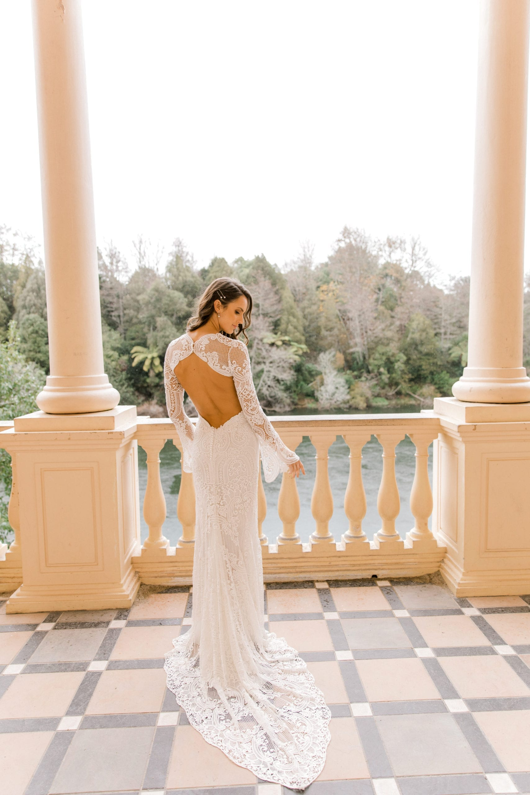 Model wearing Vinka Design Sabine Wedding Dress, a French Crochet Lace Wedding Gown on an open balcony with columns