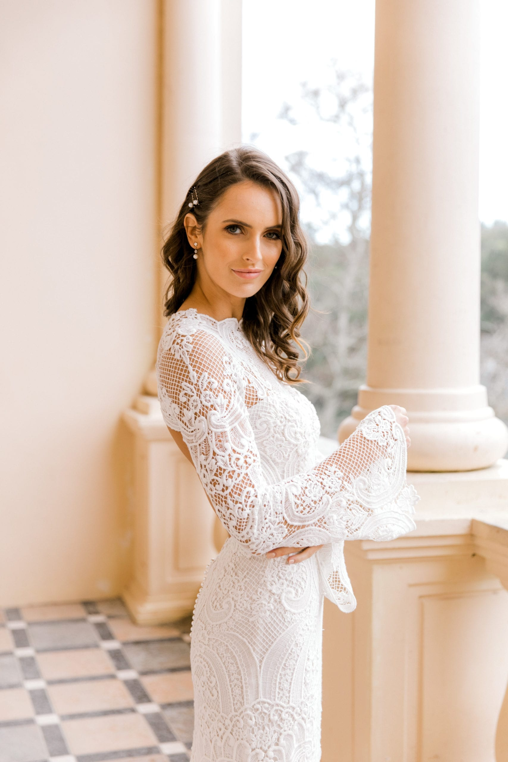 Model wearing Vinka Design Sabine Wedding Dress, a French Crochet Lace Wedding Gown on an open balcony with columns posing to the side