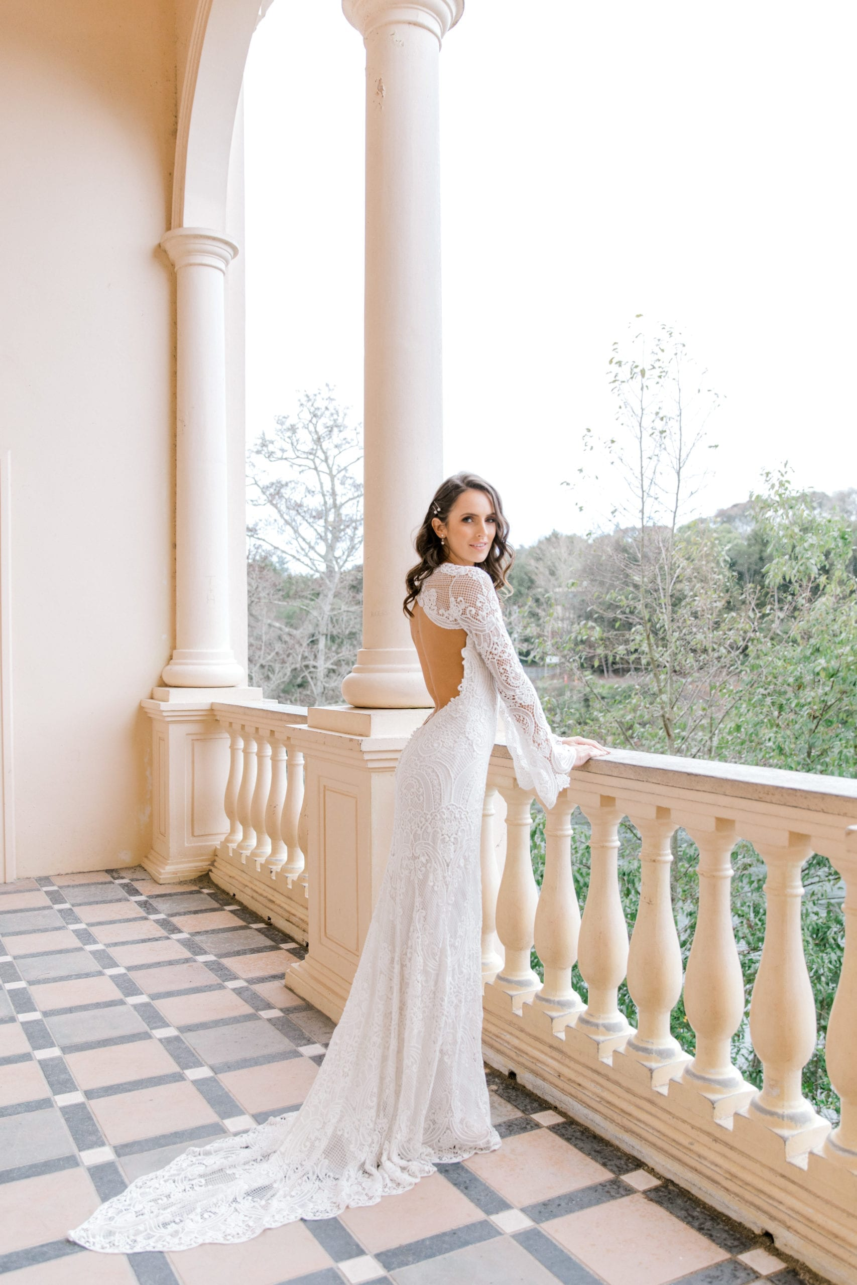 Model wearing Vinka Design Sabine Wedding Dress, a French Crochet Lace Wedding Gown on an open balcony with columns looking over garden