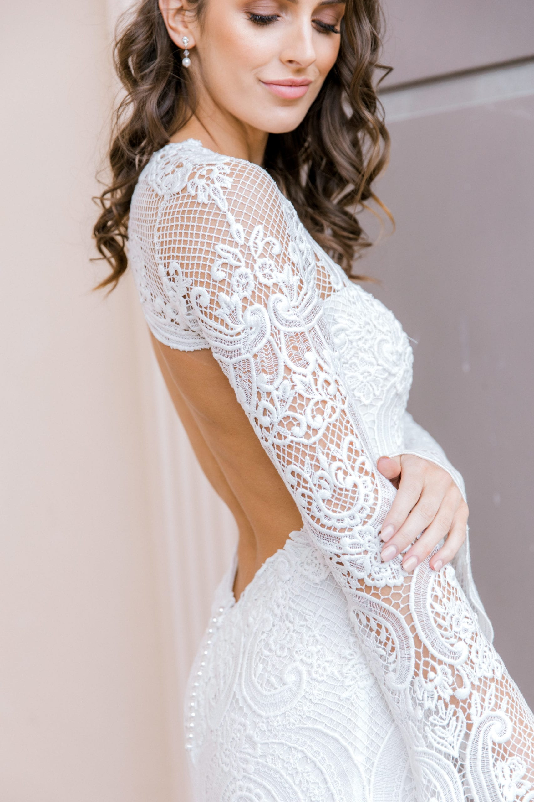 Model wearing Vinka Design Sabine Wedding Dress, a French Crochet Lace Wedding Gown close up showing low back