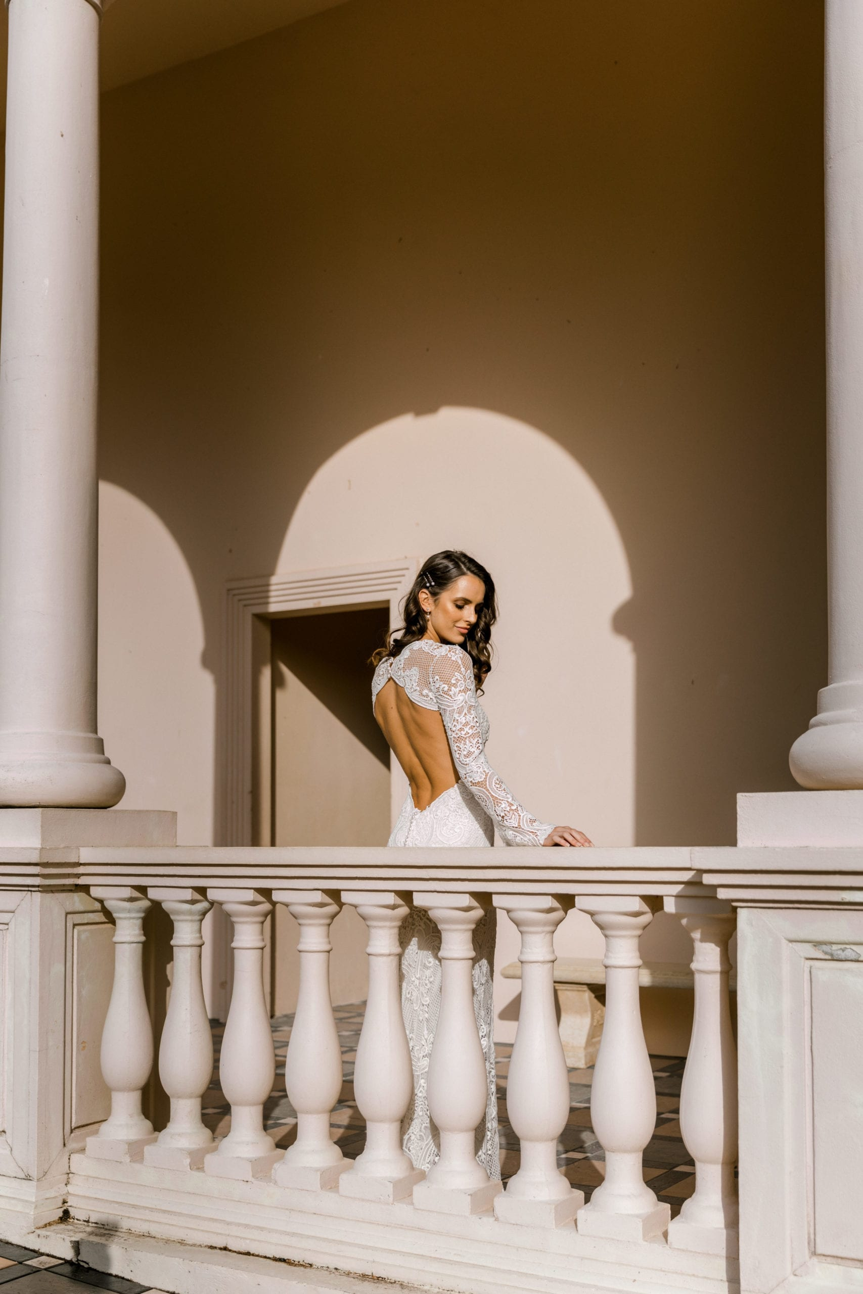 Model wearing Vinka Design Sabine Wedding Dress, a French Crochet Lace Wedding Gown over balcony under archway
