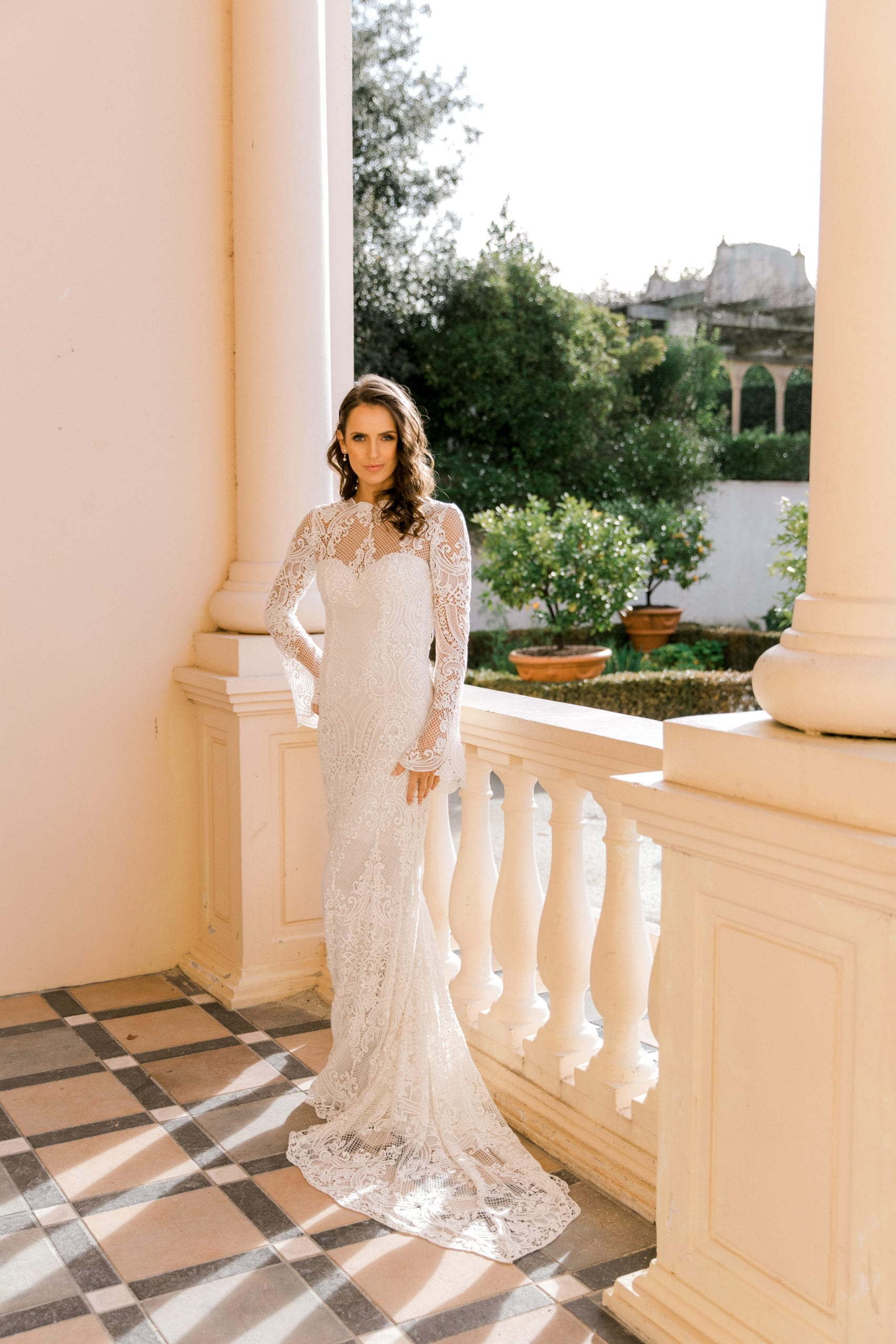 Model wearing Vinka Design Sabine Wedding Dress, a French Crochet Lace Wedding Gown on balcony with garden behind