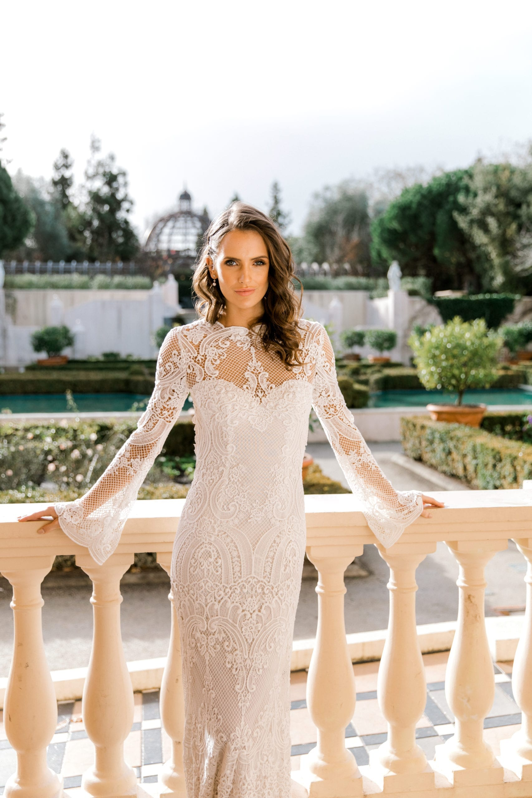 Model wearing Vinka Design Sabine Wedding Dress, a French Crochet Lace Wedding Gown leaning on balcony with garden behind