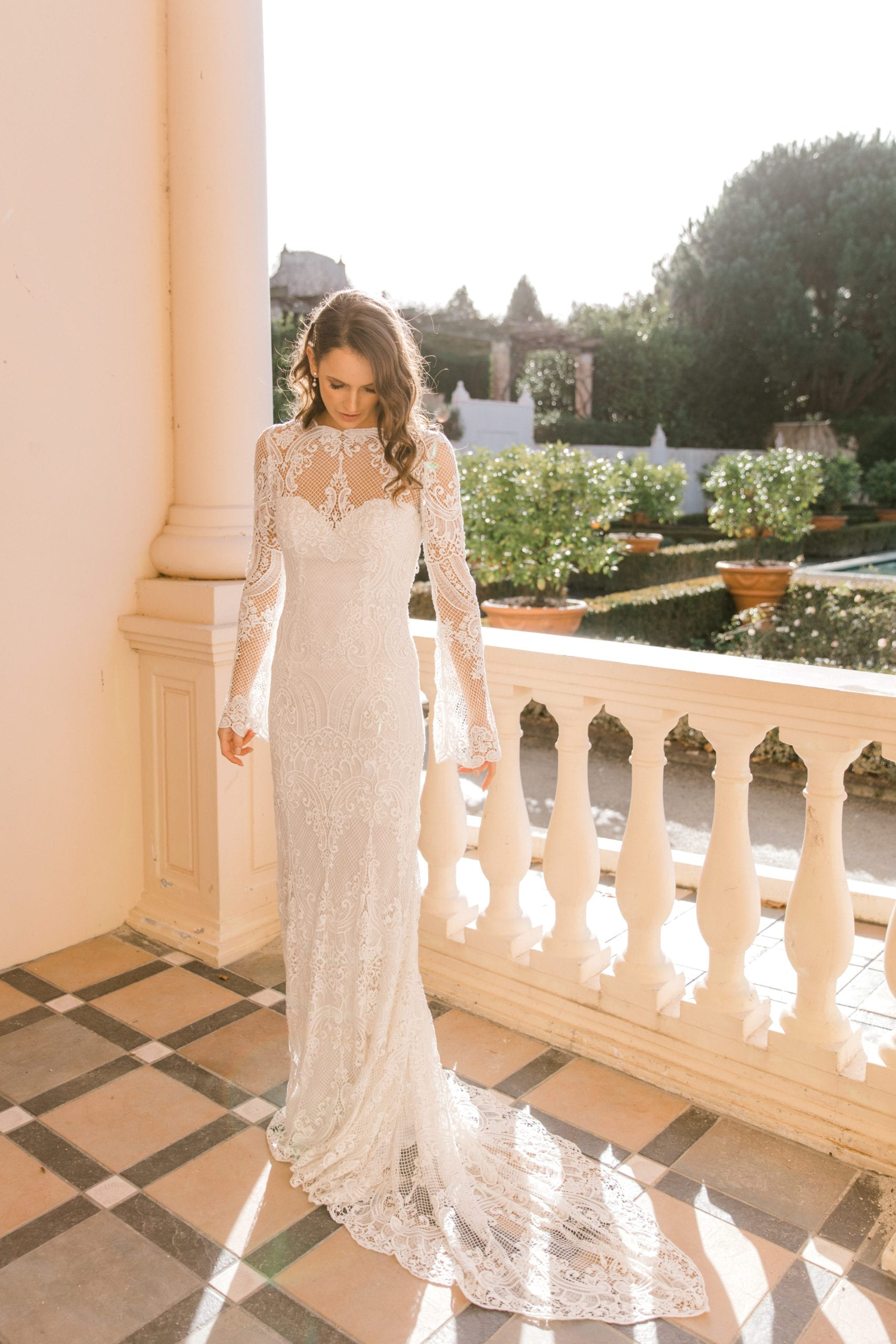 Model wearing Vinka Design Sabine Wedding Dress, a French Crochet Lace Wedding Gown on balcony with train flowing and garden behind