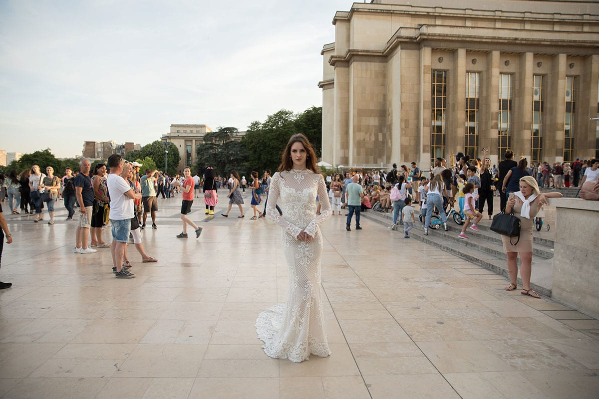Model wearing Vinka Design Hayley Wedding Dress, a Backless Long Sleeve Lace Wedding Gown in Paris