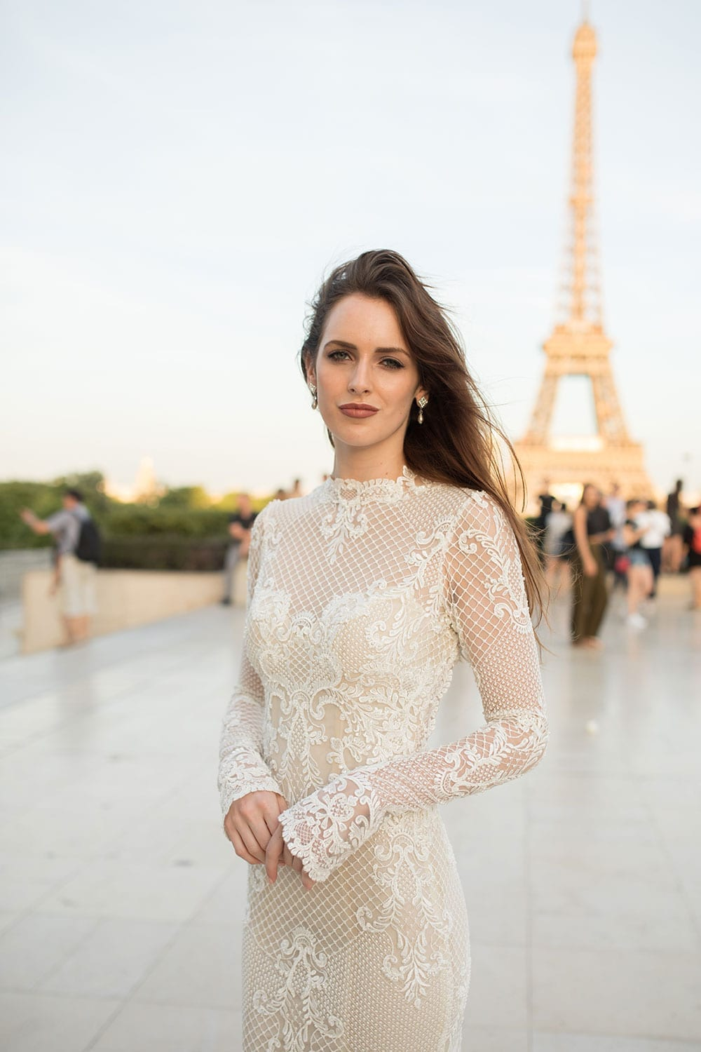 Model wearing Vinka Design Hayley Wedding Dress, a Backless Long Sleeve Lace Wedding Gown in front of the Eiffel Tower in Paris