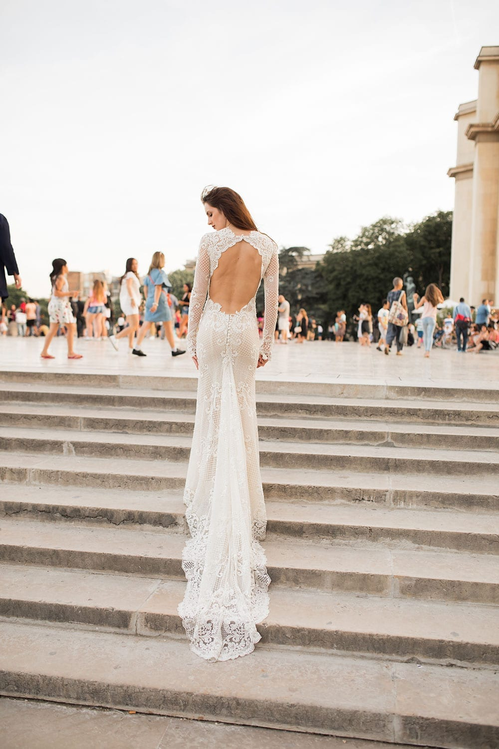 Model wearing Vinka Design Hayley Wedding Dress, a Backless Long Sleeve Lace Wedding Gown on marble steps in Paris