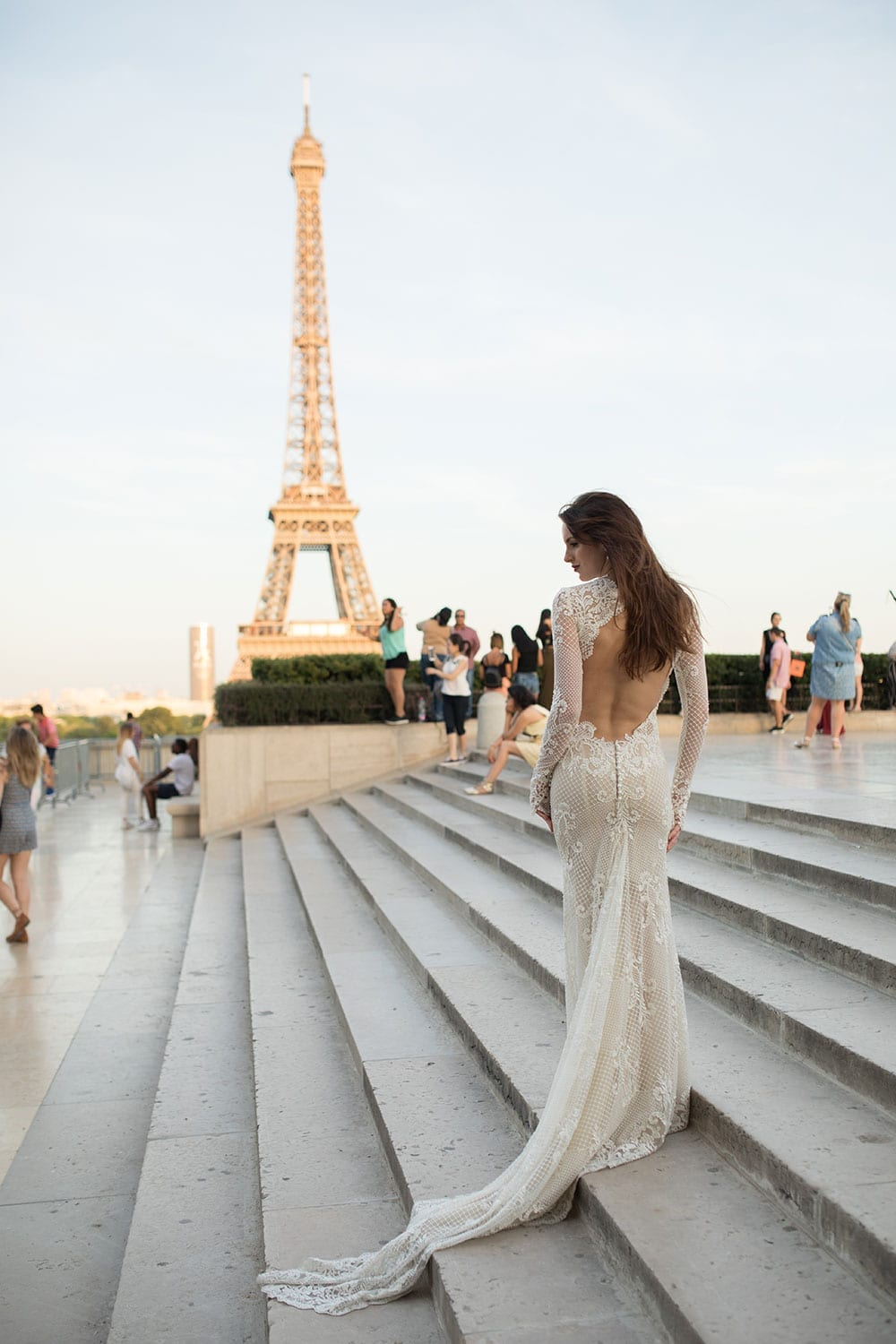 Model wearing Vinka Design Hayley Wedding Dress, a Backless Long Sleeve Lace Wedding Gown on the marble steps in Paris with the Eiffel Tower in the background