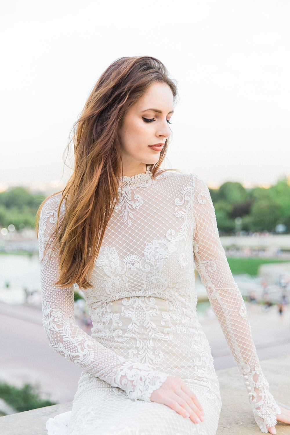 Model wearing Vinka Design Hayley Wedding Dress, a Backless Long Sleeve Lace Wedding Gown sitting outdoors in Paris
