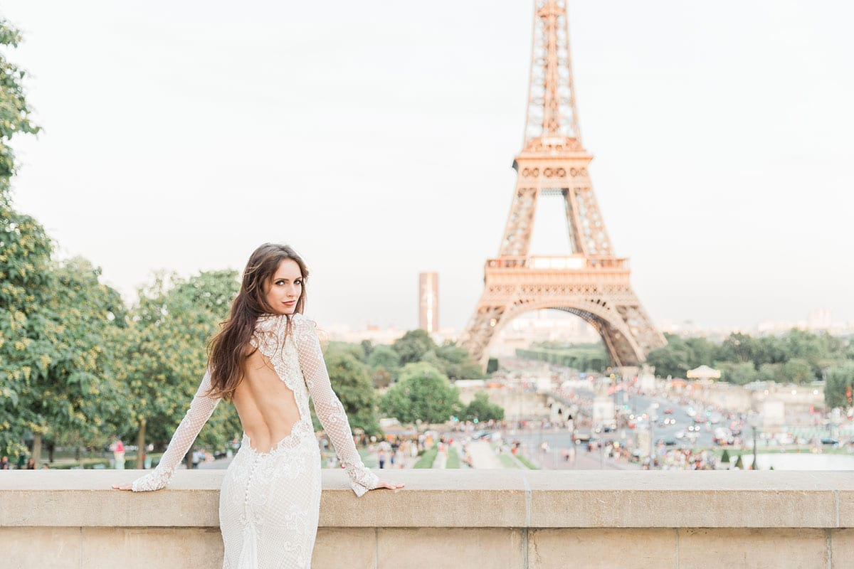 Model wearing Vinka Design Hayley Wedding Dress, a Backless Long Sleeve Lace Wedding Gown looking over a bridge in Paris towards the Eiffel Tower
