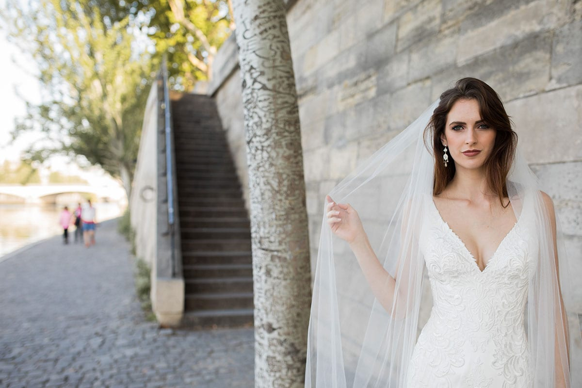 Model wearing Vinka Design Joanna Wedding Dress, a Deep V-Neck Fitted Lace Wedding Gown along the river in Paris