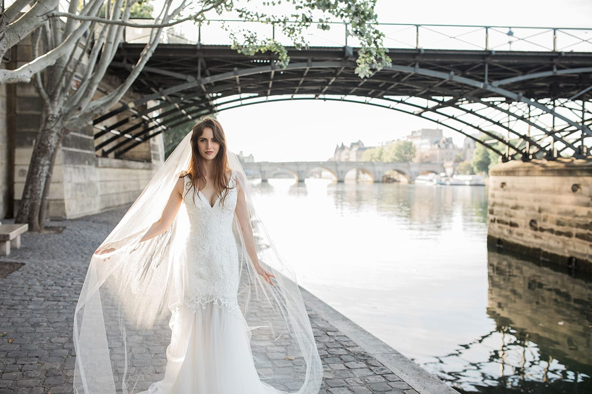 Model wearing Vinka Design Joanna Wedding Dress, a Deep V-Neck Fitted Lace Wedding Gown walking along the river in Paris showing flowing train of dresswith arms stretched showing the layers