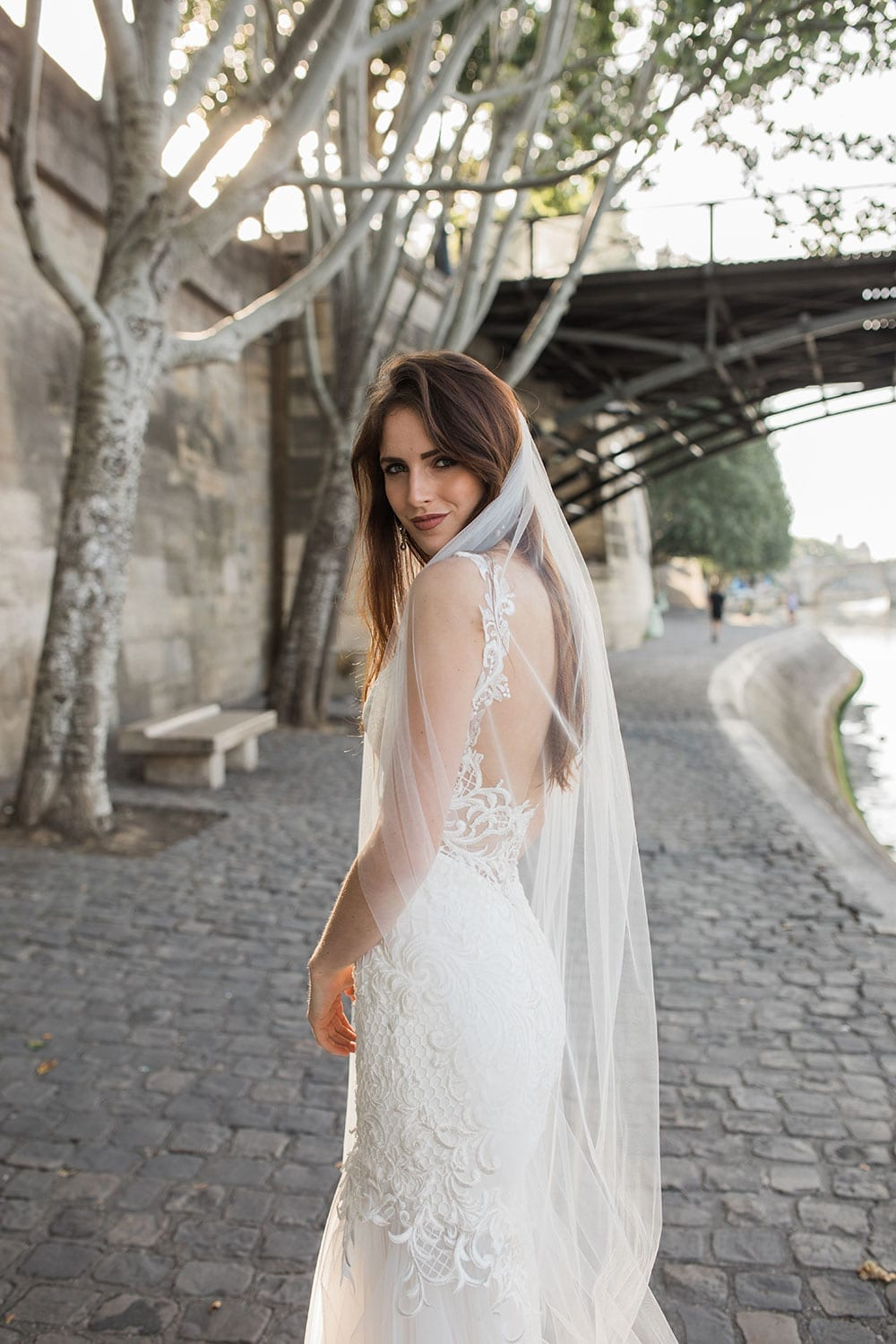 Model wearing Vinka Design Joanna Wedding Dress, a Deep V-Neck Fitted Lace Wedding Gown walking along the river in Paris showing back of dress