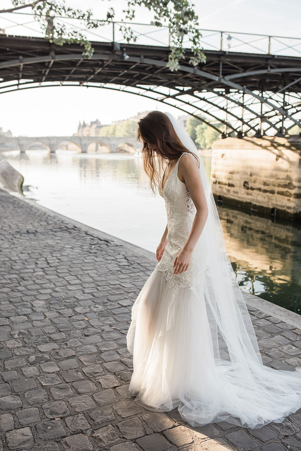 Model wearing Vinka Design Joanna Wedding Dress, a Deep V-Neck Fitted Lace Wedding Gown walking along the river in Paris showing flowing train of dress
