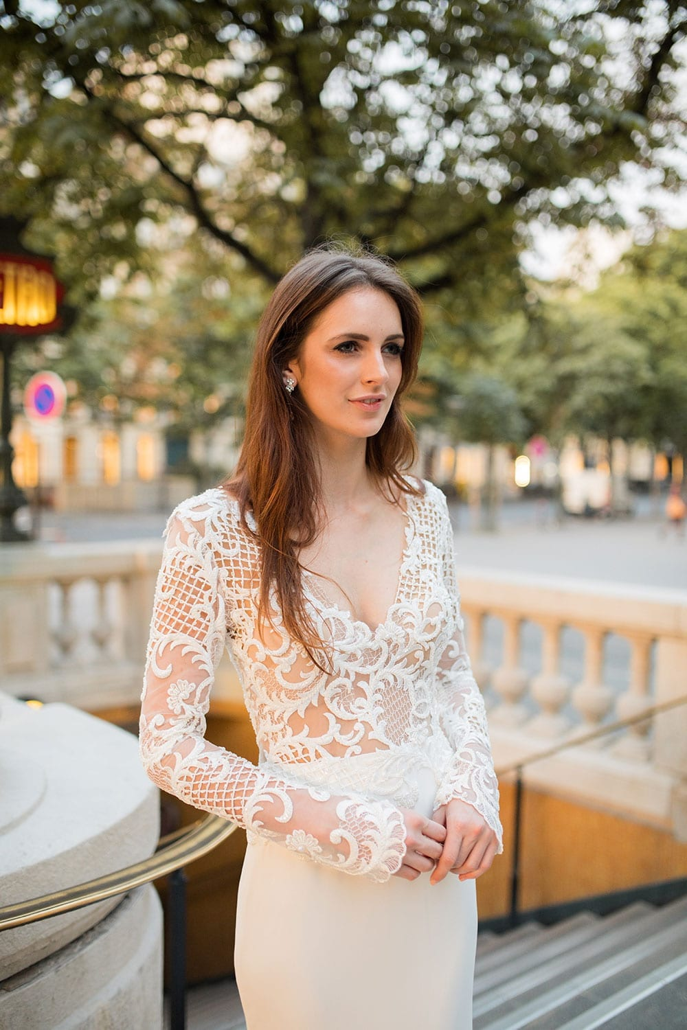 Model wearing Vinka Design Katrina Wedding Dress, a Sheer Beaded Lace Wedding Gown with long sleeves and a train worn on the streets of Paris