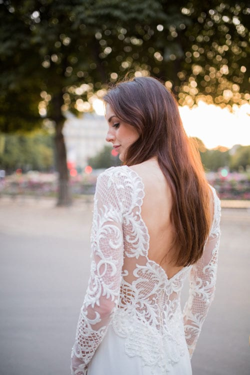 Model wearing Vinka Design Katrina Wedding Dress, a Sheer Beaded Lace Wedding Gown on a Paris street with back of dress detail close up
