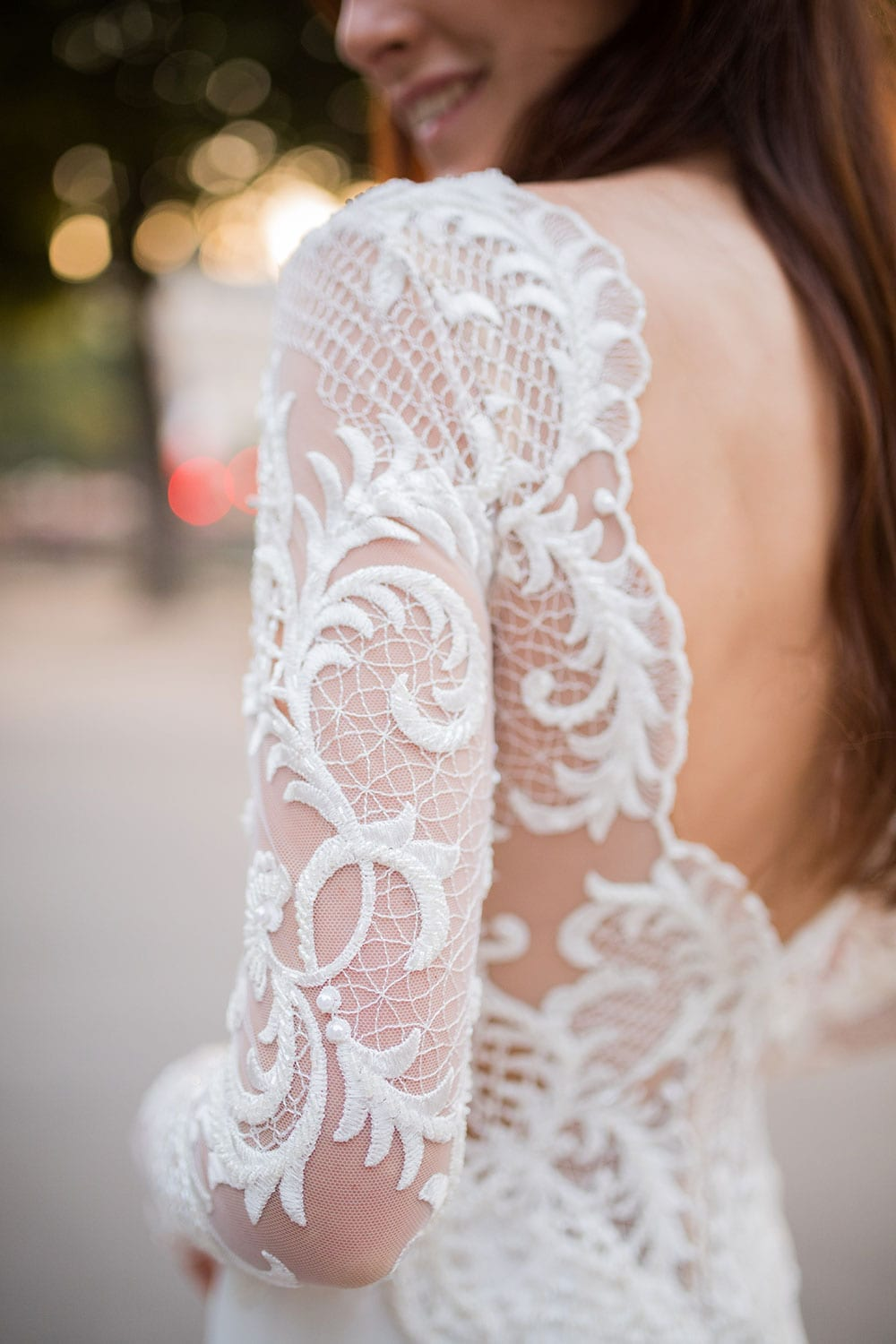 Model wearing Vinka Design Katrina Wedding Dress, a Sheer Beaded Lace Wedding Gown with long sleeves and a train close up of back and sleeve lace detail