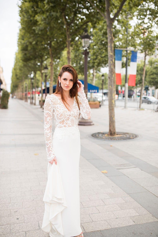Model wearing Vinka Design Katrina Wedding Dress, a Sheer Beaded Lace Wedding Gown walking along a Paris street