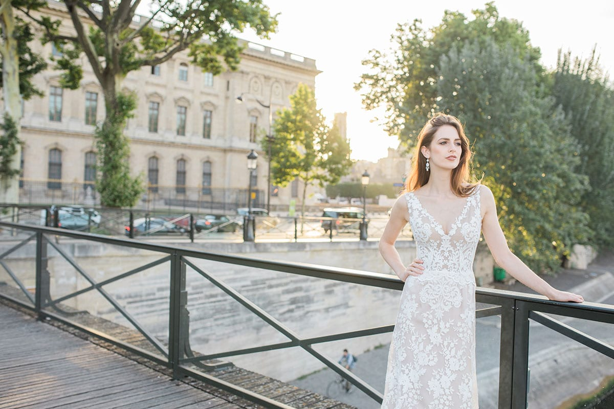 Model wearing Vinka Design Kerrie Wedding Dress, a V-Neck Lace Gown on Blush Silk Base with Low Back on a bridge with a Parisian chateau in the background