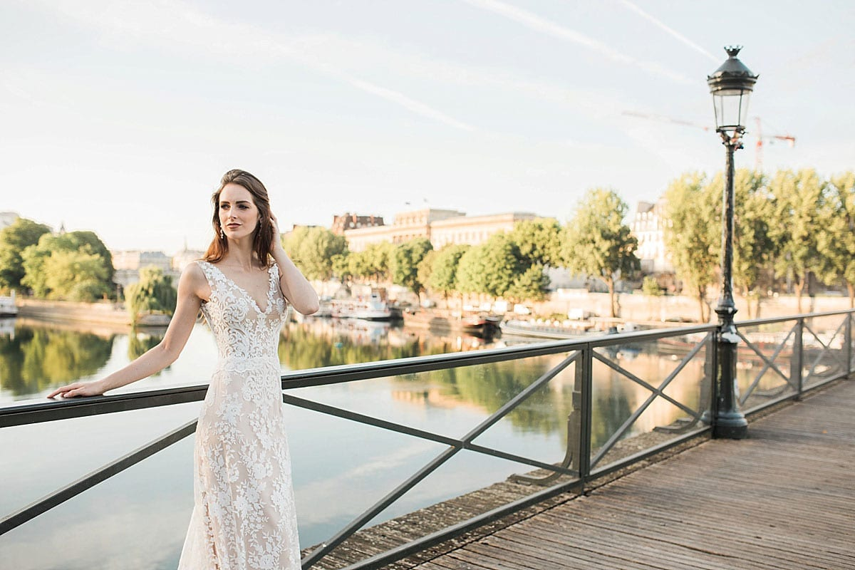 Model wearing Vinka Design Kerrie Wedding Dress, a V-Neck Lace Gown on Blush Silk Base with Low Back on a Parisian bridge