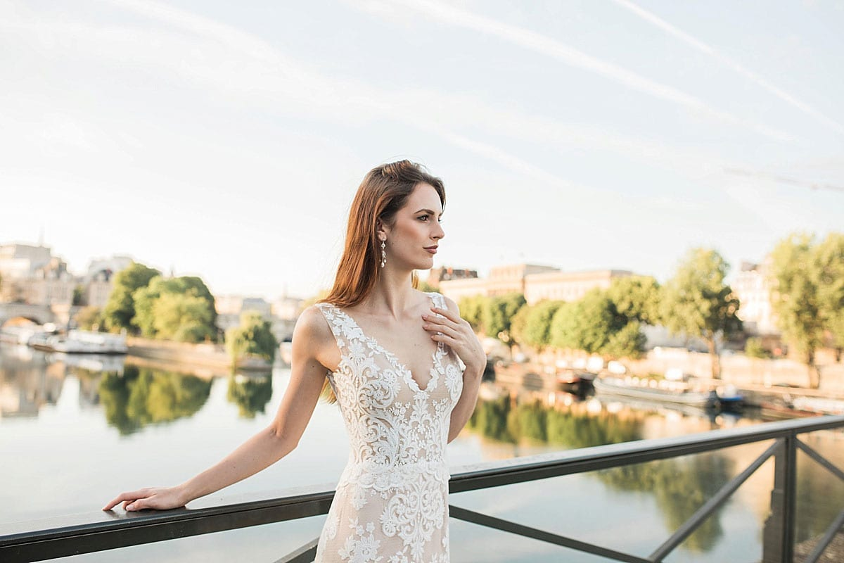 Model wearing Vinka Design Kerrie Wedding Dress, a V-Neck Lace Gown on Blush Silk Base with Low Back leaning against a bridge in Paris