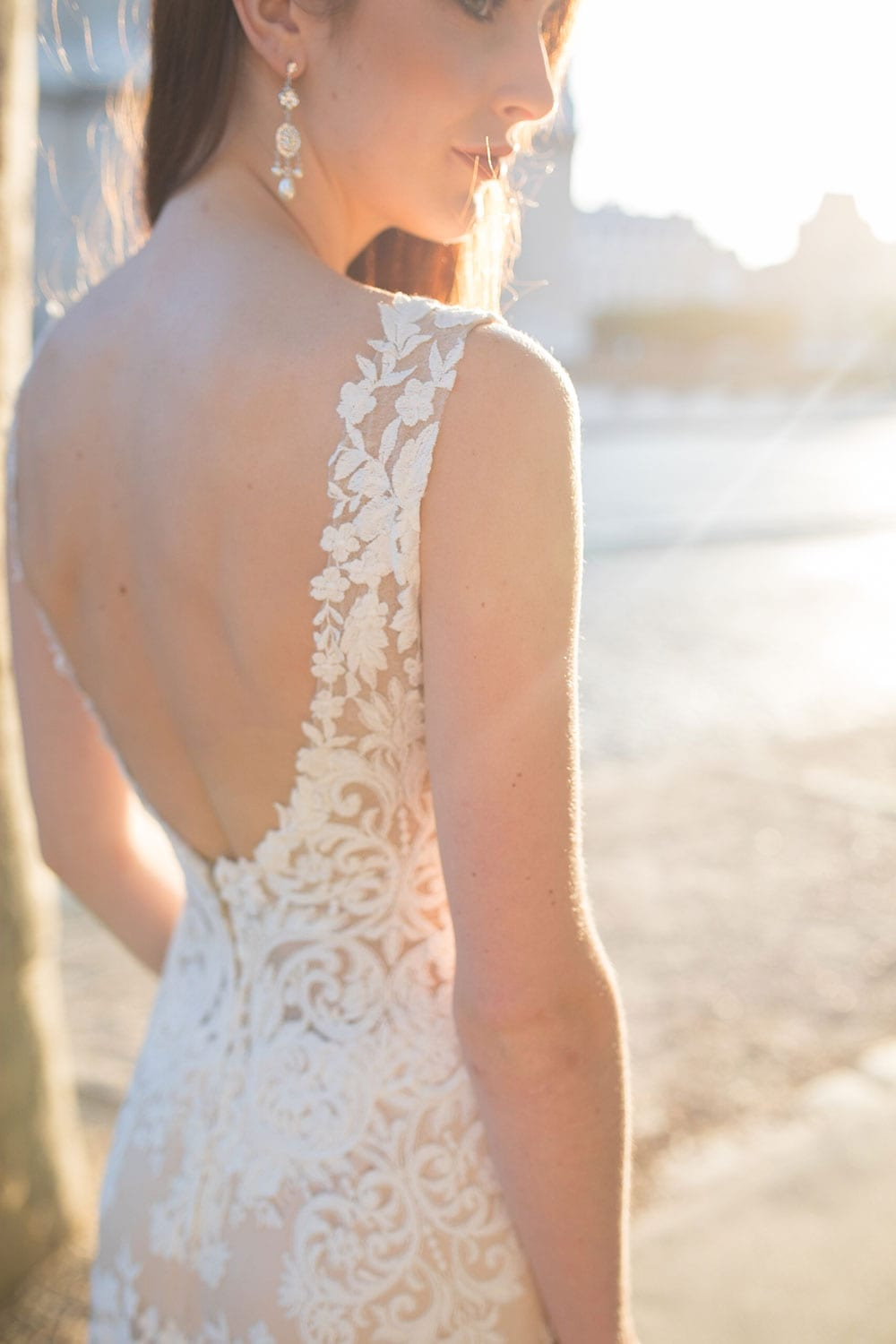 Model wearing Vinka Design Kerrie Wedding Dress, a V-Neck Lace Gown on Blush Silk Base with Low Back outside a Parisian chateau
