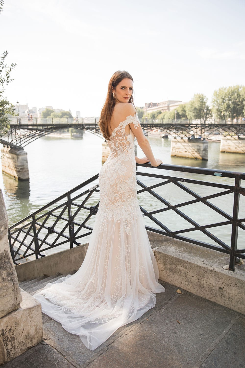 Model wearing Vinka Design Sashia Wedding Dress, an Off-Shoulder Fitted Lace and Tulle Gown on Paris balcony