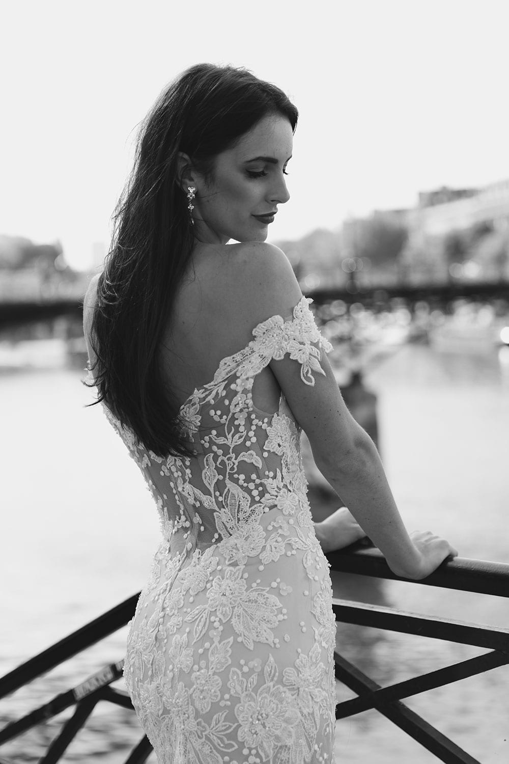 Model wearing Vinka Design Sashia Wedding Dress, an Off-Shoulder Fitted Lace and Tulle Gown on Paris balcony looking to river in black and white