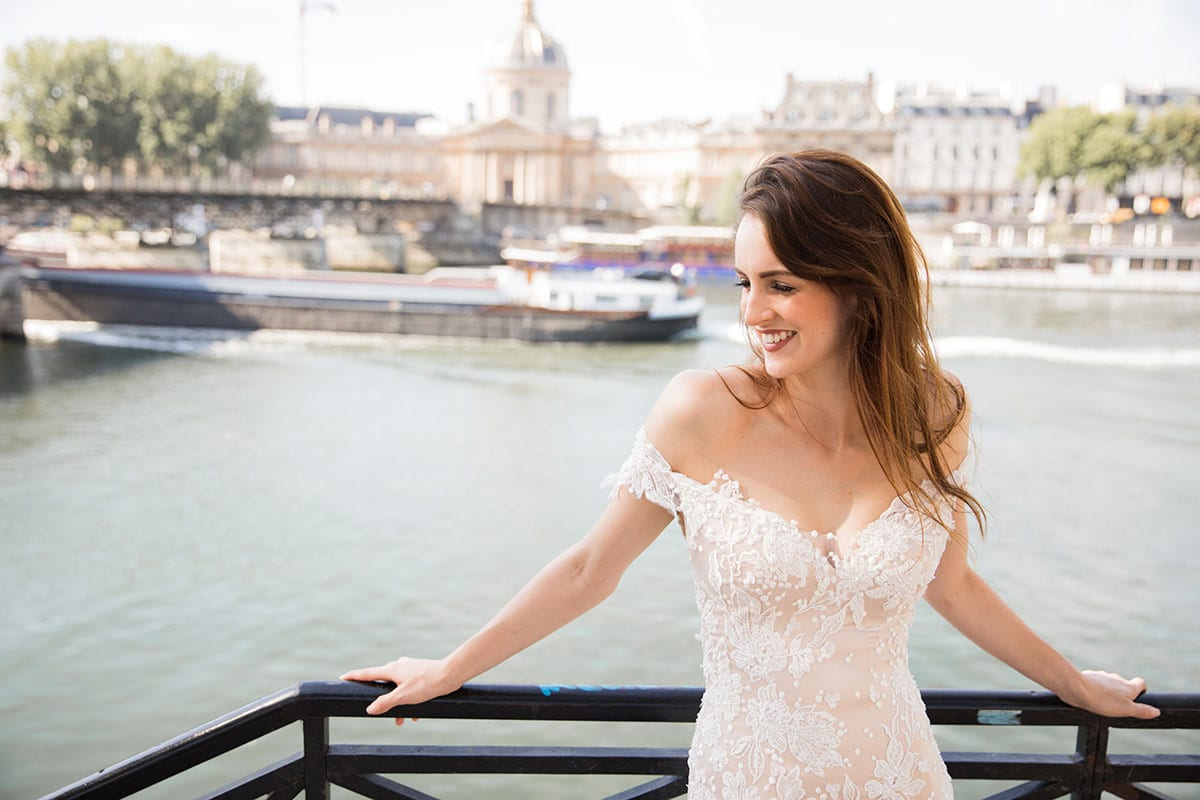 Model wearing Vinka Design Sashia Wedding Dress, an Off-Shoulder Fitted Lace and Tulle Gown leaning against Paris balcony