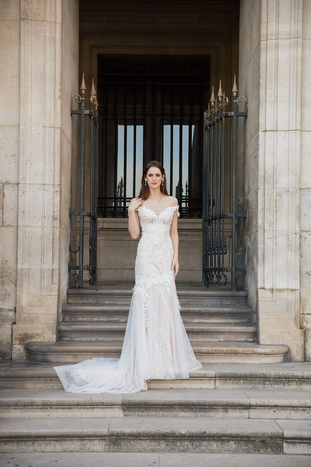 Model wearing Vinka Design Sashia Wedding Dress, an Off-Shoulder Fitted Lace and Tulle Gown on steps in Paris