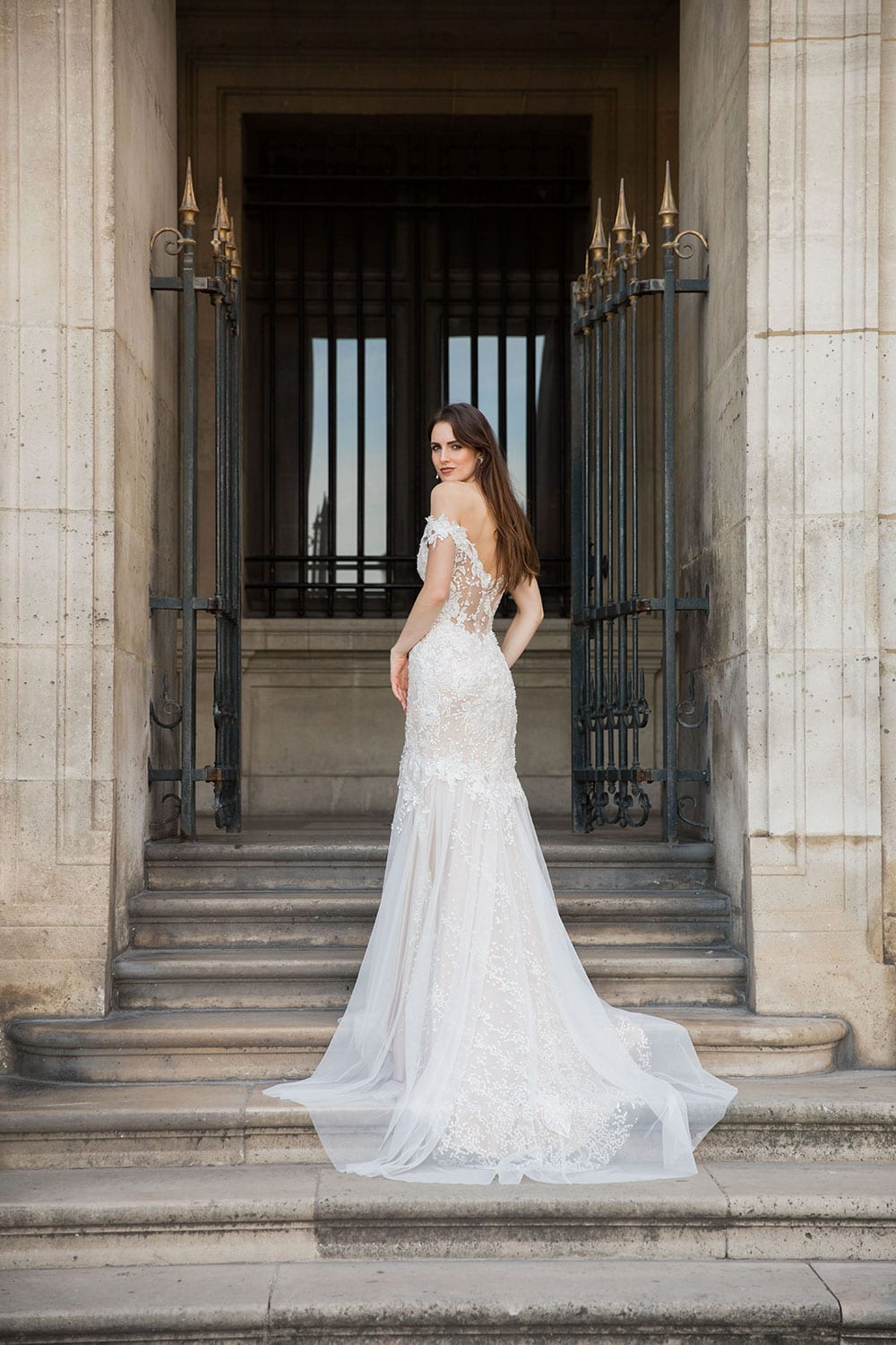 Model wearing Vinka Design Sashia Wedding Dress, an Off-Shoulder Fitted Lace and Tulle Gown looking over shoulder on steps in Paris