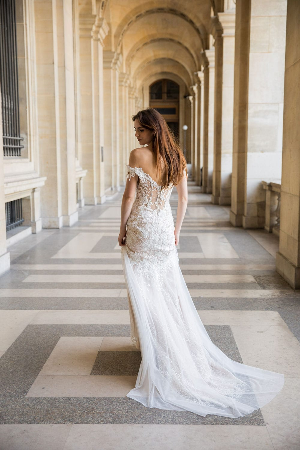Model wearing Vinka Design Sashia Wedding Dress, an Off-Shoulder Fitted Lace and Tulle Gown in long corridor of archways in building in Paris