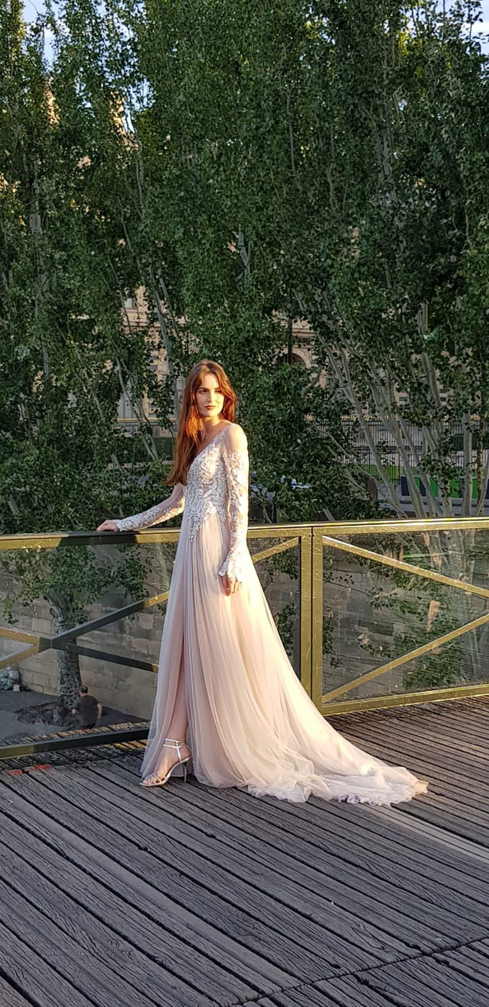 Model wearing Vinka Design Suri Wedding Dress, a Backless Silver Tulle and Lace Gown with Long Sleeves posed on Paris boardwalk
