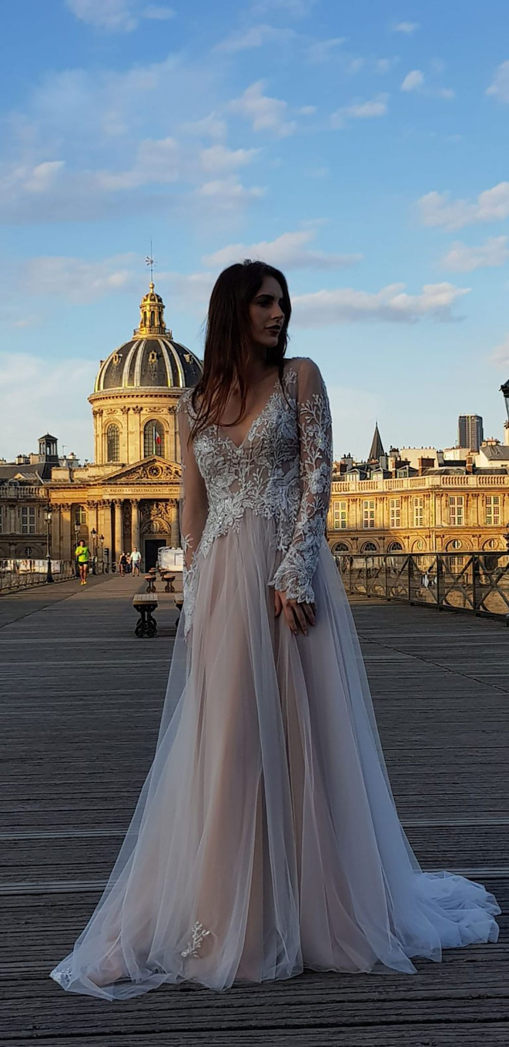 Model wearing Vinka Design Suri Wedding Dress, a Backless Silver Tulle and Lace Gown with Long Sleeves dress flowing in Paris street