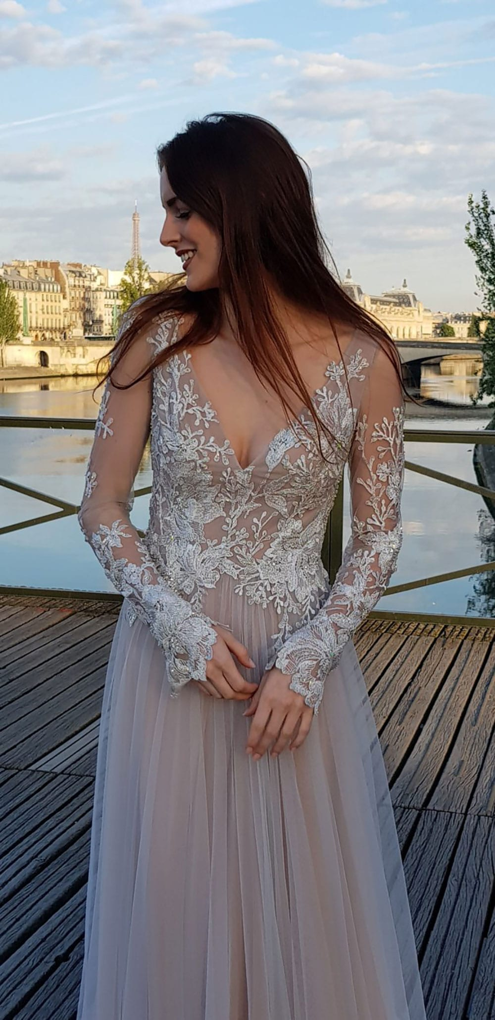 Model wearing Vinka Design Suri Wedding Dress, a Backless Silver Tulle and Lace Gown with Long Sleeves hands together in front on Paris boardwalk
