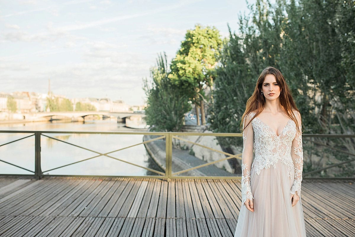 Model wearing Vinka Design Suri Wedding Dress, a Backless Silver Tulle and Lace Gown with Long Sleeves on a boardwalk with Paris backdrop